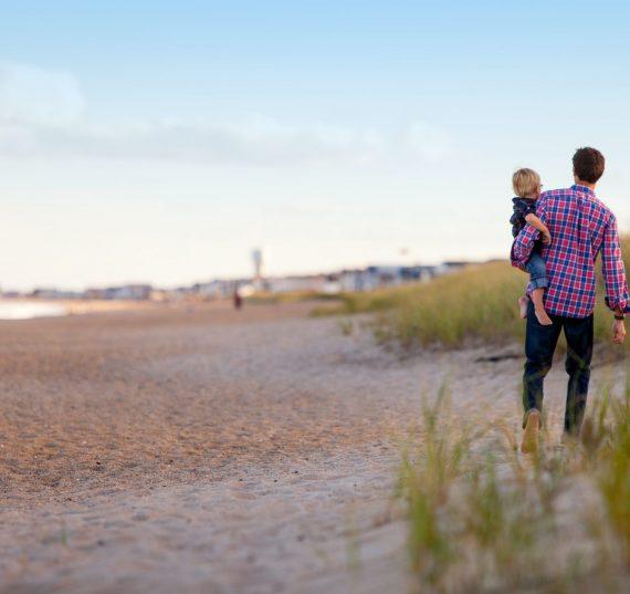 Padre sujetando a su hijo mientras da un paseo por una playa vacía al lado de unas dunas naturales. El hombre lleva una camisa a cuadros de color rojo y azul.